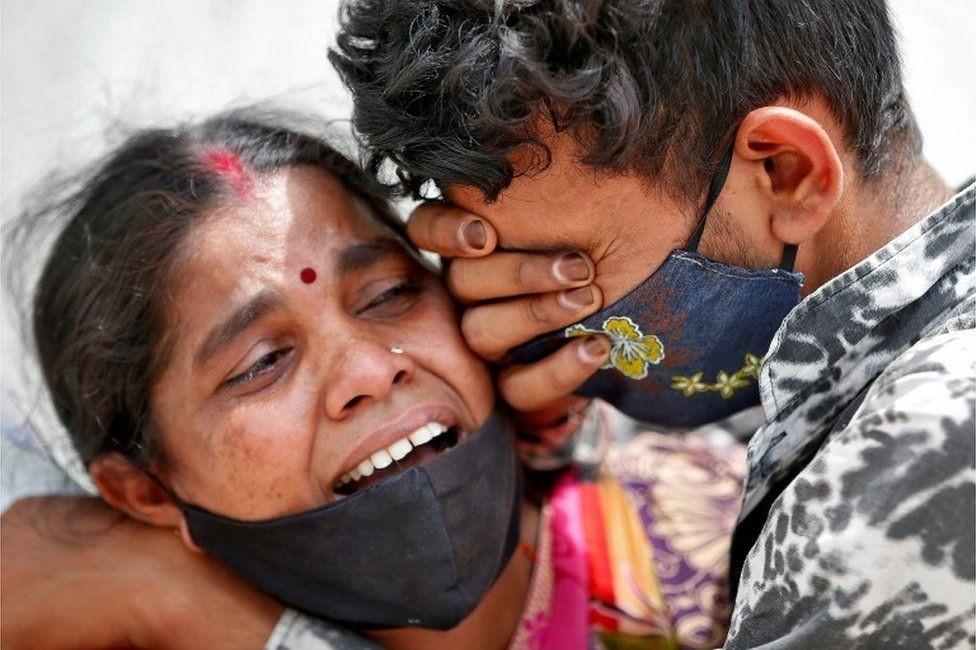 شخصان يبكيان بعد موت أحد أقاربهما في الهند