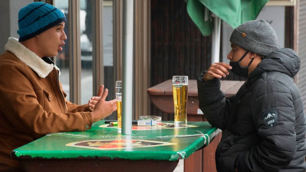 Two men enjoy some beers at a streetside bar in the city centre in Cape Town, on August 18, 2020.
