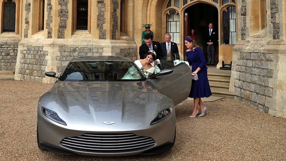 Jack Brooksbank and Princess Beatrice help Eugenie into the Aston Martin
