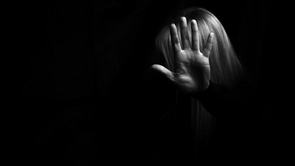 Mujer protegiéndose con mano