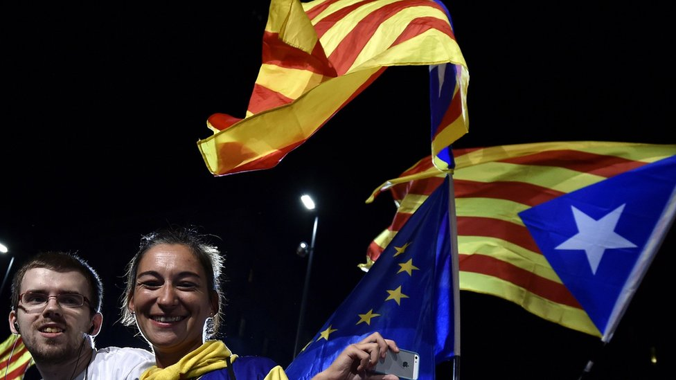 Catalan independence supporters celebrate as they wave European and Catalan flags 27 September 2015