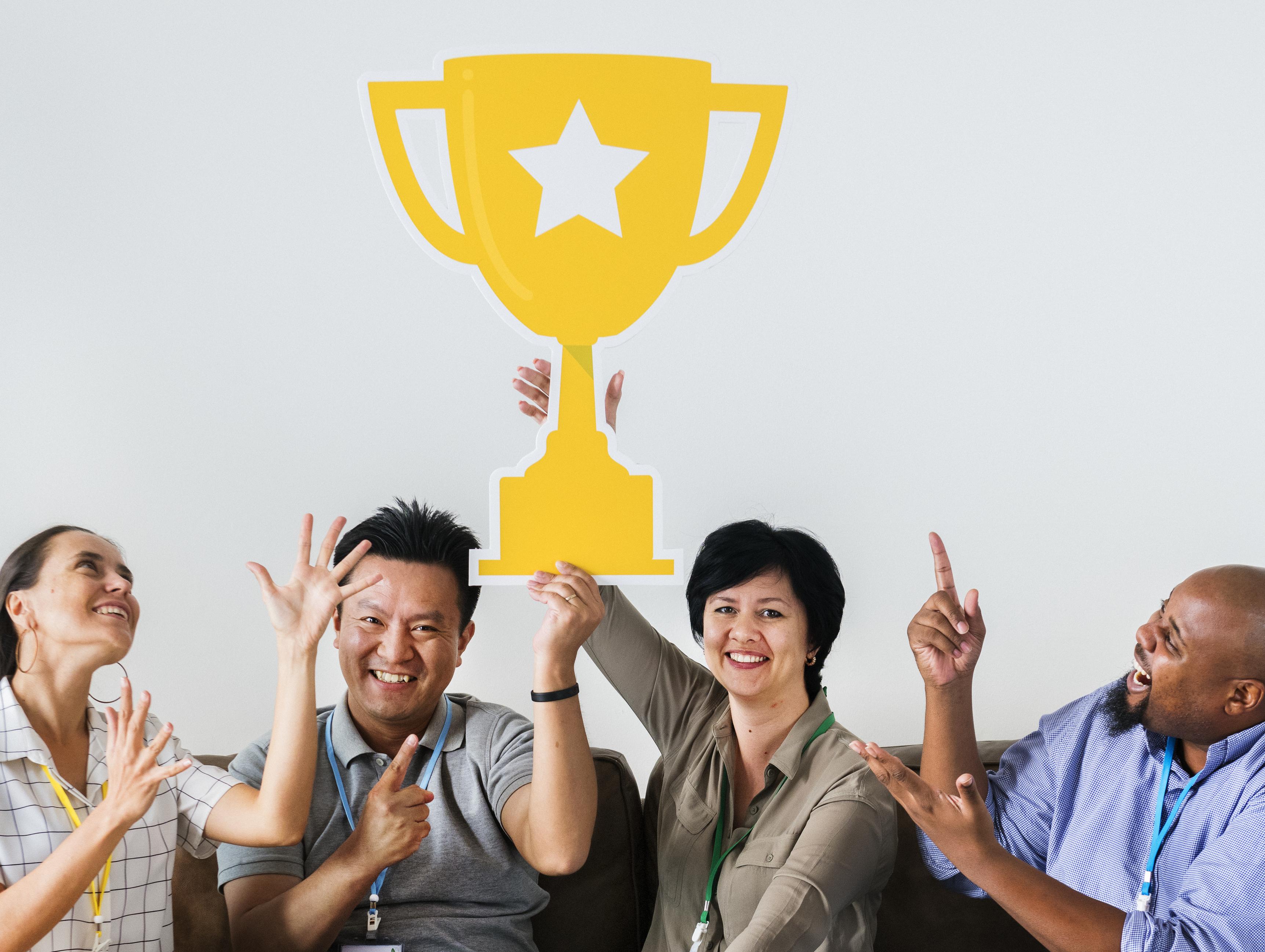 Grupo de trabajadores sosteniendo un trofeo.