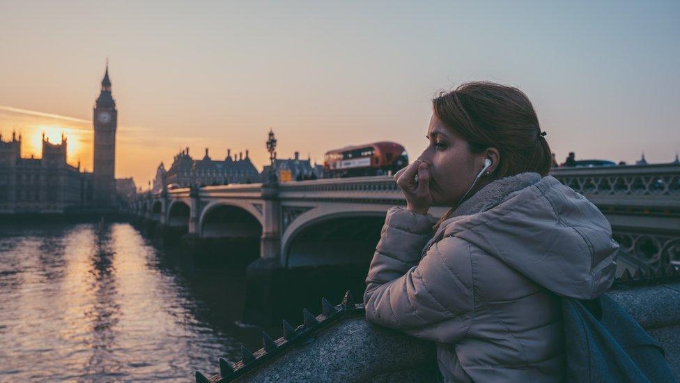 Mujer en Londres con audífonos.