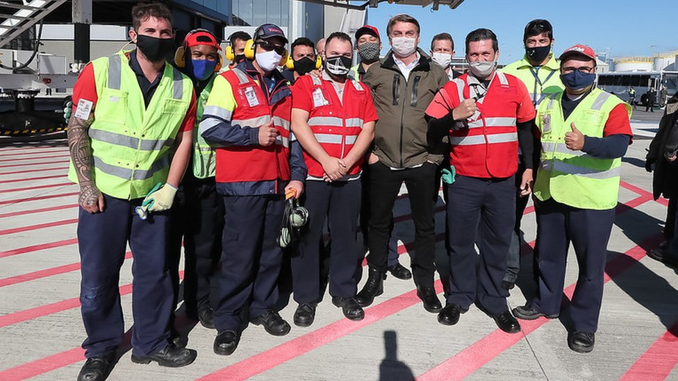 De máscara, presidente posa para foto rodeado por operadores de voo em pátio de decolagem