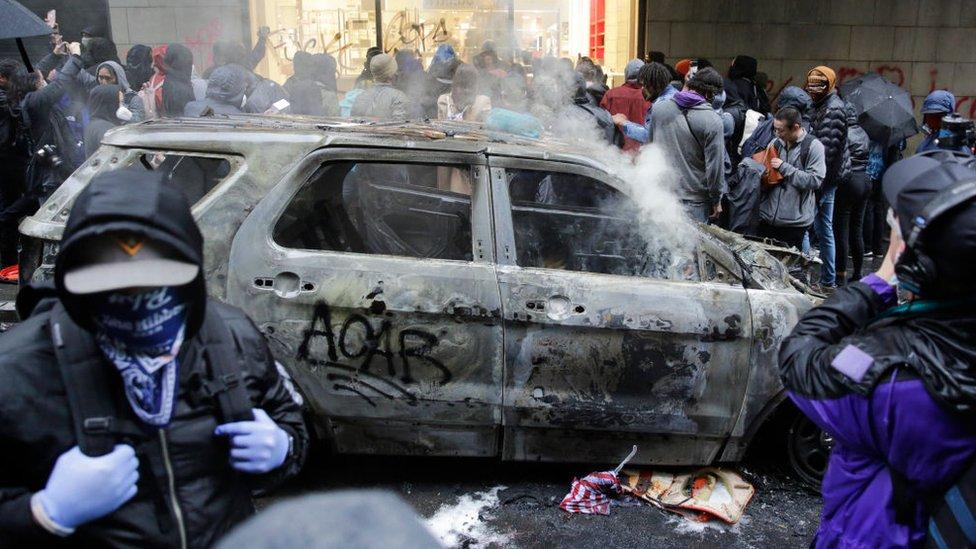 Manifestantes junto a un auto quemado en Seattle.