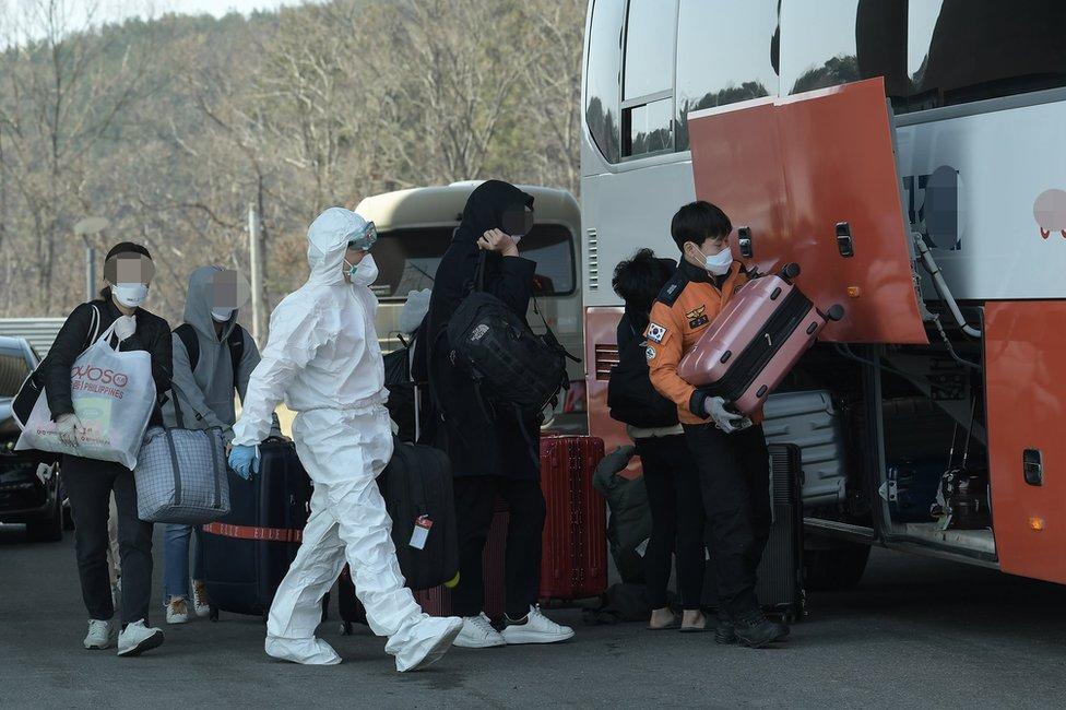Passengers from London load their baggage on a bus after undergoing COVID-19 tests at a hotel near Incheon International Airport, in Incheon, South Korea, 23 March 2020, to be bussed to a facility for their two-week isolation.