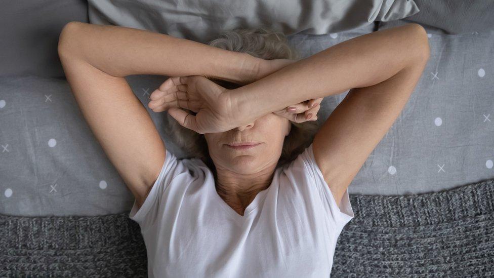 Una mujer en la cama con dificultades para dormir se cubre los ojos con los brazos
