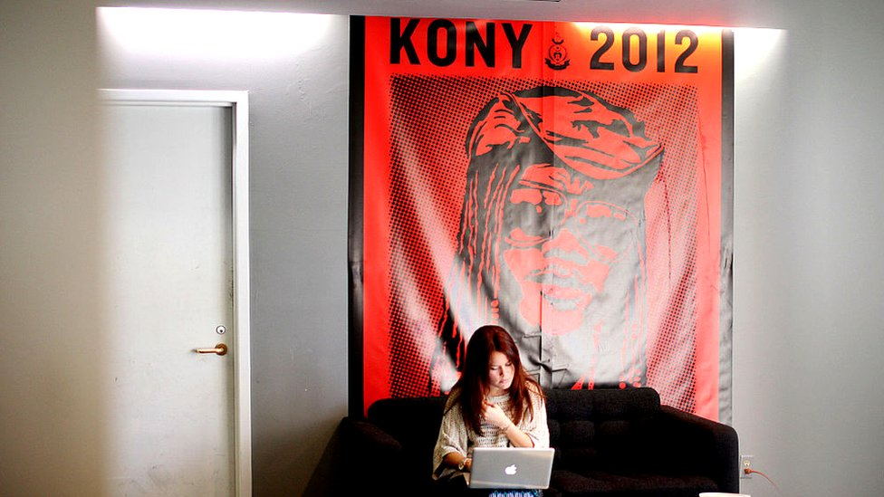 Woman sitting in front of Kony 2012 poster