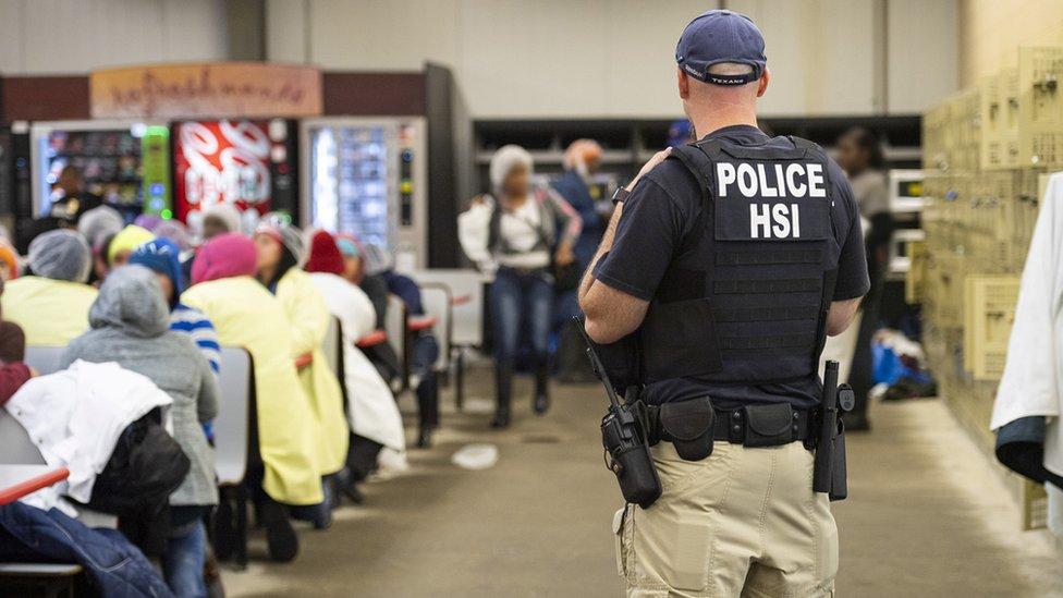 Un agente migratorio vigilando a un grupo de inmigrantes