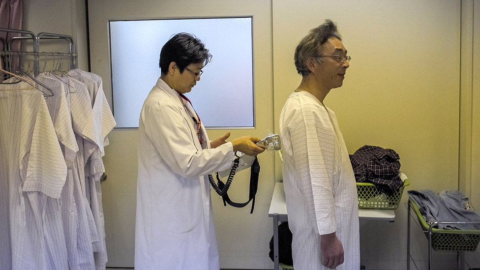 A doctor prepares a patient to be screened for radiation just outside the 20km evacuation zone surrounding the tsunami-crippled Fukushima Dai-ichi nuclear plant