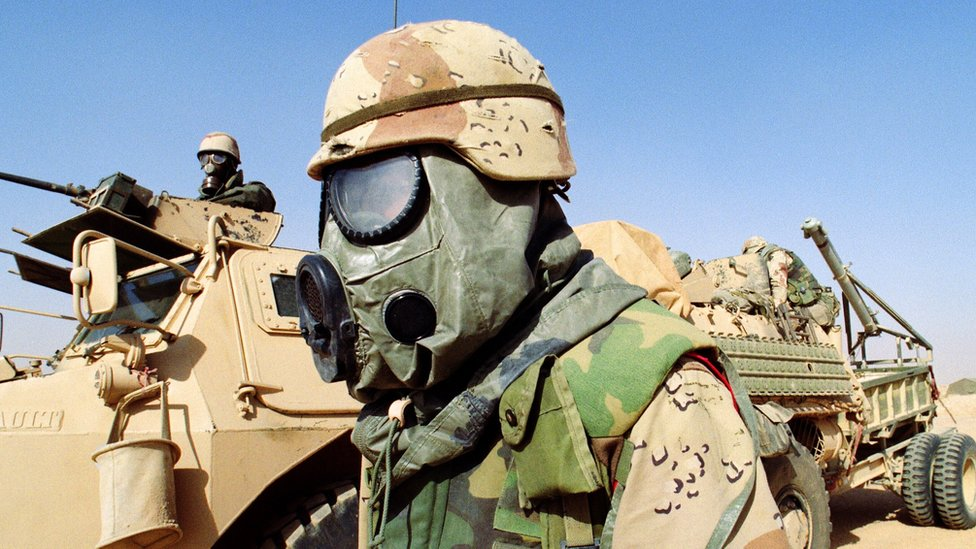 A US soldier (C) stands 09 February 1991 somewhere in Saudi Arabian desert in front of a French armored vehicle (VAB) from the 6th Foreign Legion Engineers Regiment. Both soldiers are wearing chemical warfare equipment.