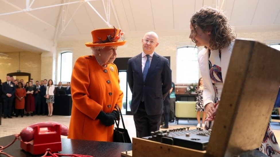 The Queen looking at Enigma machine