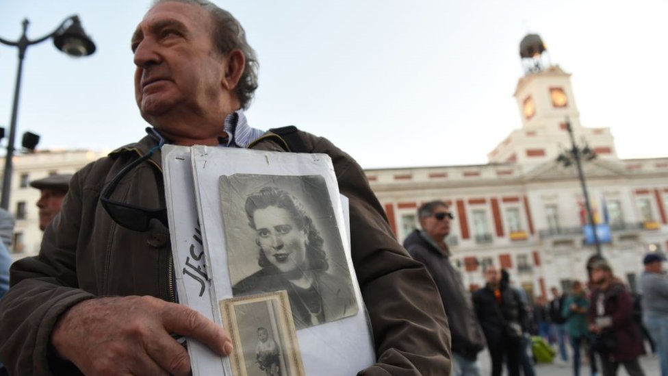 A man holds a picture of a woman who went missing under Franco