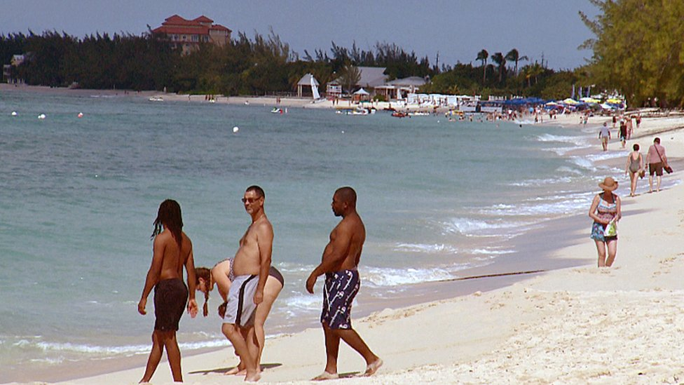 tourists on a beach in Grand Cayman