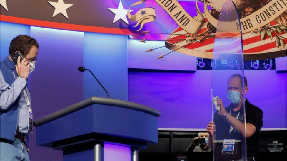 A worker cleans the plexiglass shields onstage at the site of the final debate between U.S. President Trump and former Vice President Biden in Nashville, Tennessee worker cleans the plexiglass shields onstage at the site of the final debate between U.S. President Trump and former Vice President Biden in Nashville, Tennessee
