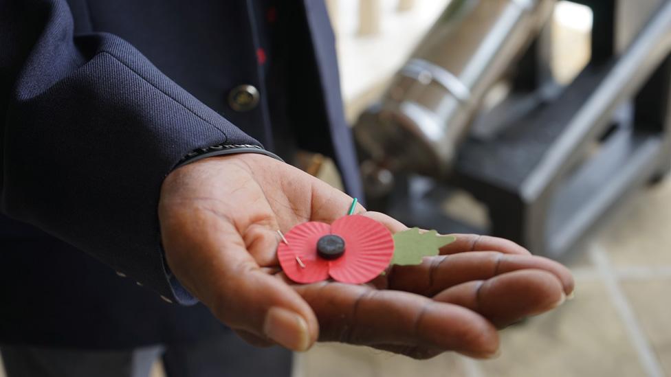 An ex-serviceman holds a poppy