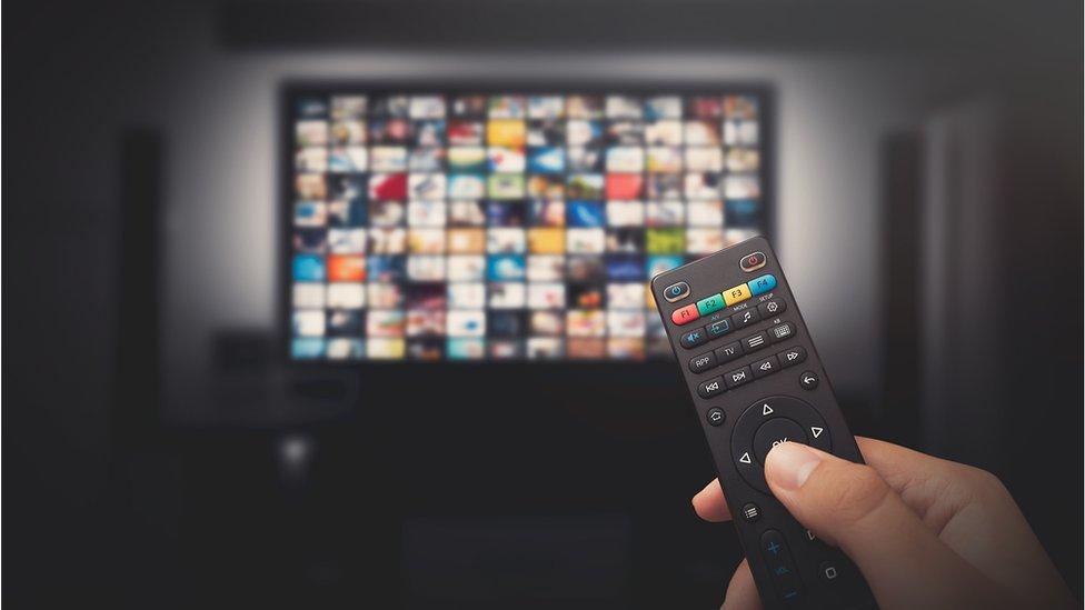 شخص يمسك بجهز تحكم قبالة التلفزيون