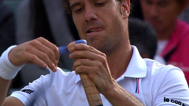 Richard Gasquet applies a new grip to his racquet
