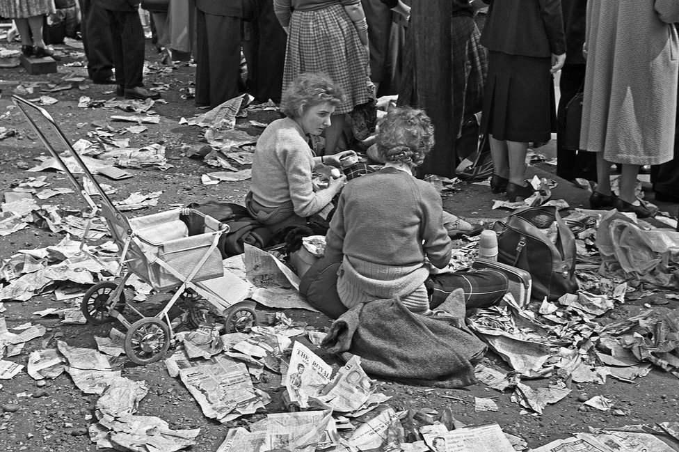 Two women enjoying a picnic amid newspapers on the ground, Royal Wedding