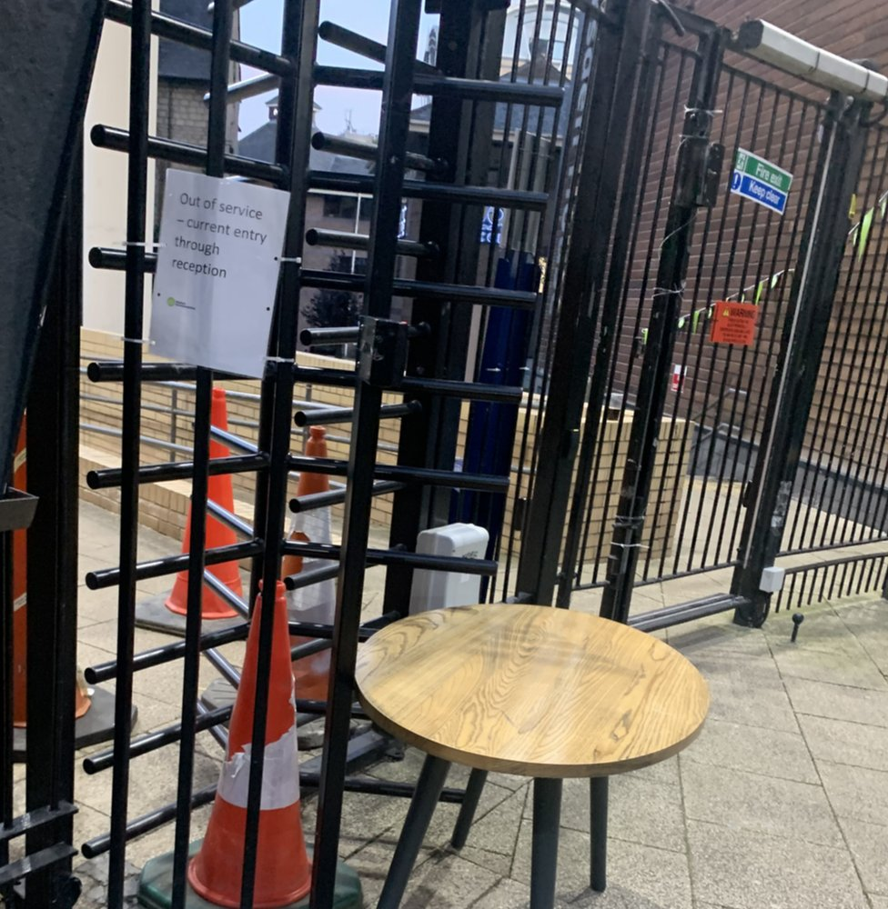 Turnstile with chair and a road works cone blocking it