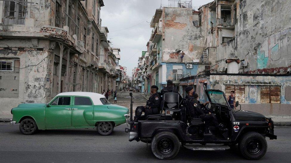 Una unidad de las fuerzas especiales se cruza con un auto clásico en La Habana