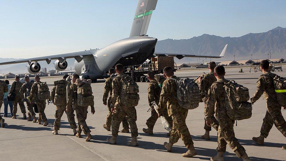 Soldados estadounidenses marchan hacia un avión de transporte en la base aérea de Bagram, 11 de mayo de 2013