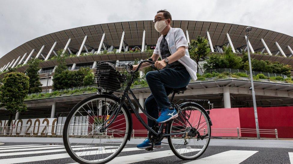 Um homem anda de bicicleta pelo estádio olímpico