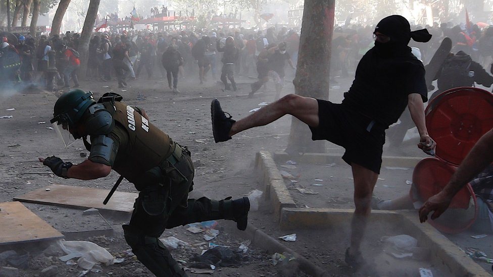 Demonstrators clash with police during a protest in the central Plaza Italia in Santiago, Chile, 12 November 2019.