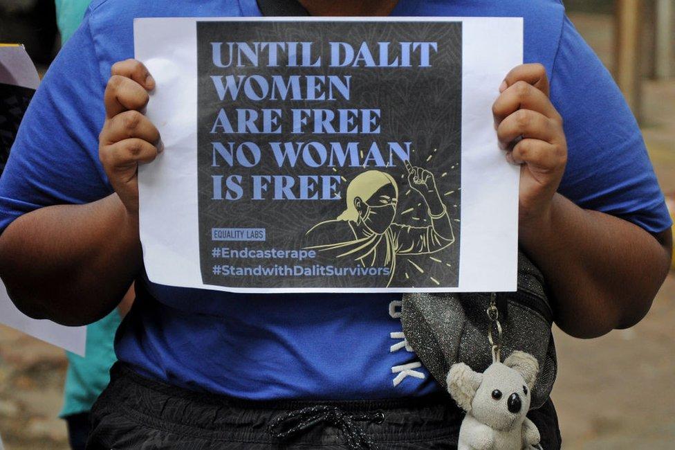 متظاهر يحمل لافتة خلال مظاهرة ضد العنف الجنسي القائم على الطائفة.