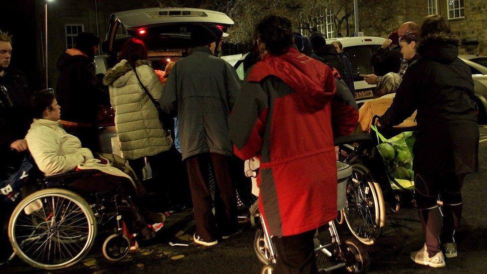 Personas recibiendo comida caliente.