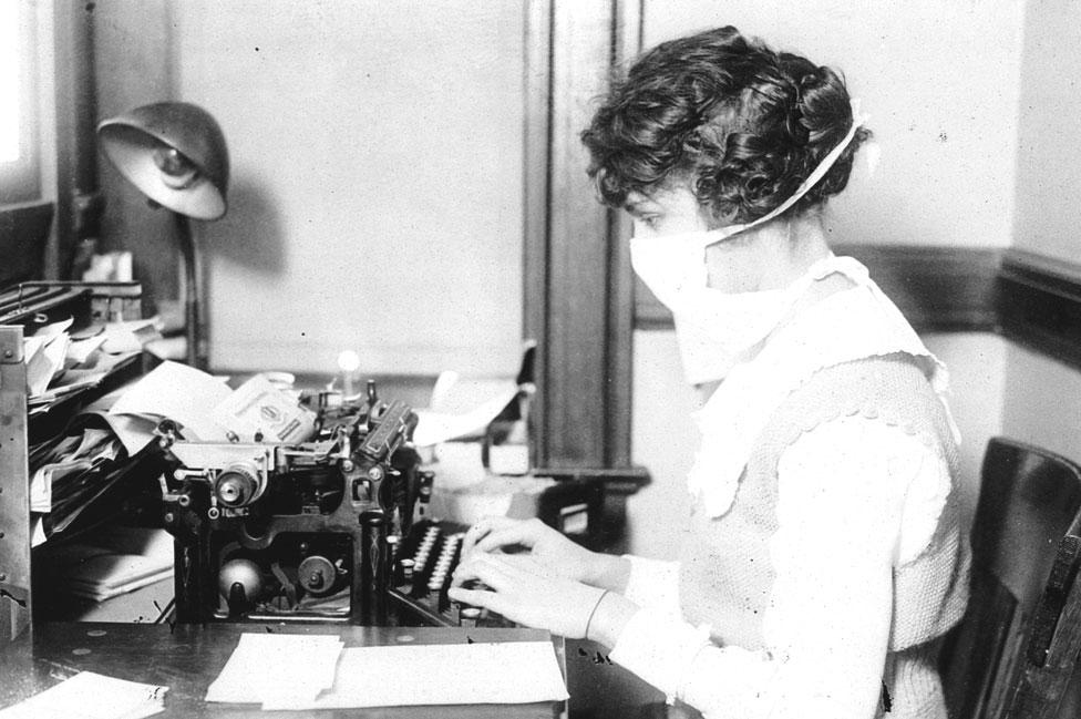 Mujer escribiendo a máquina usando una máscara en 1918.