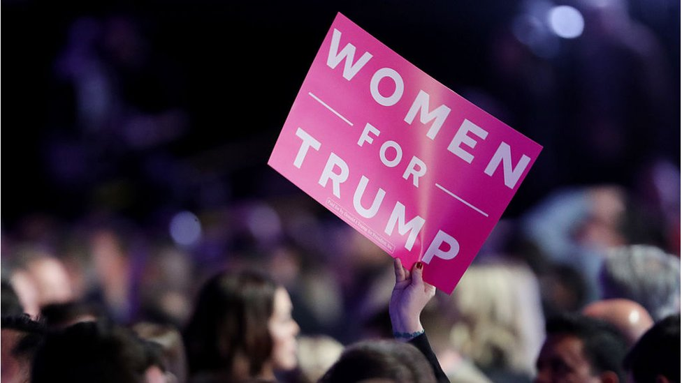 """An attendee holds up a sign in support of Republican presidential nominee Donald Trump that reads """"Women For Trump"""" during the election night event in 2016"""