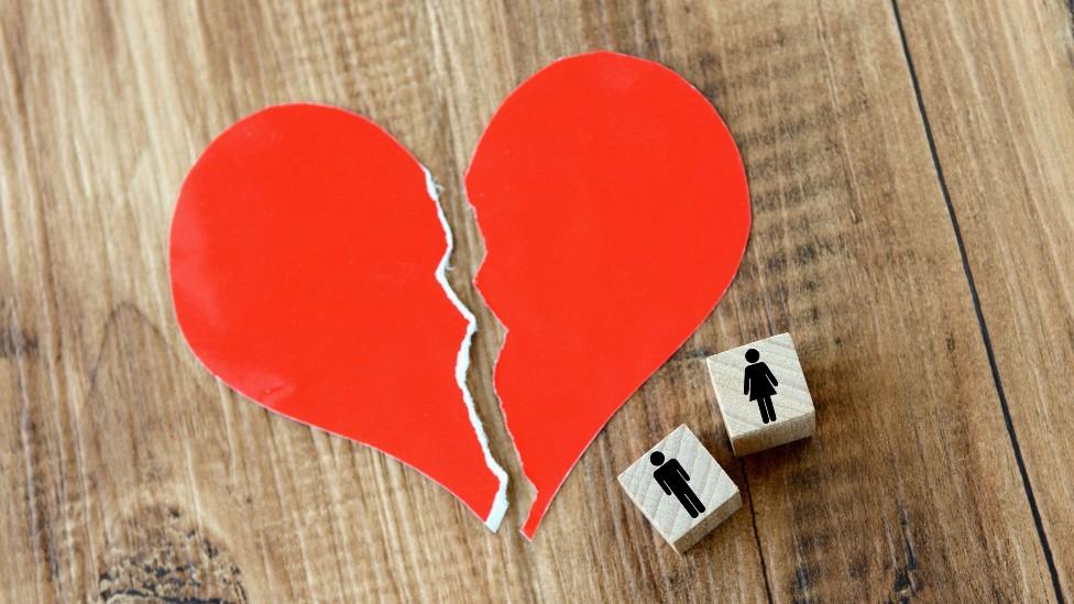 Un corazón de papel roto, con dos piezas de madera al lado que representan un hombre y una mujer