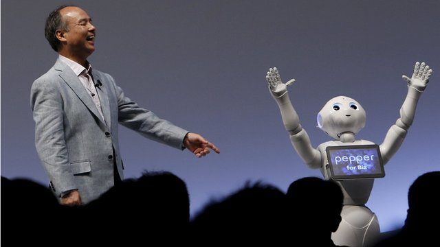 "SoftBank Group Corp. Chairman and CEO Masayoshi Son reacts as SoftBank""s human-like robots named ""Pepper"" performs during the SoftBank World 2015 event in Tokyo"