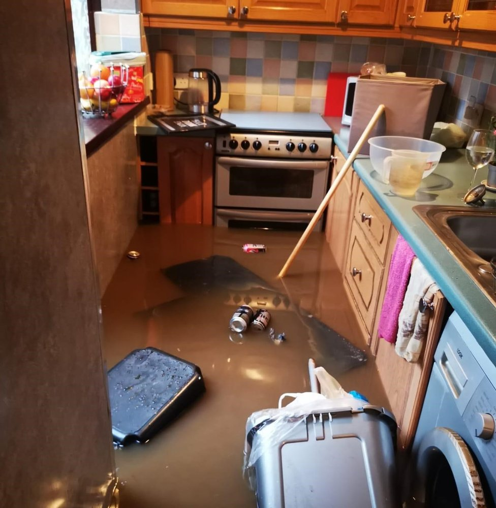 The kitchen flooded, with bins and rubbish floating in brown water, partially submerging the cooker