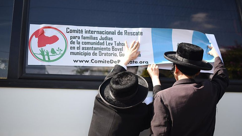 Miembros de Lev Tahor cuelgan una pancarta en un autobús en Guatemala, en 2016