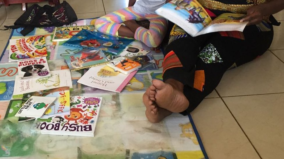 Beverley Nambozo reading with her daughter Zion, aged seven, in Kampala, Uganda