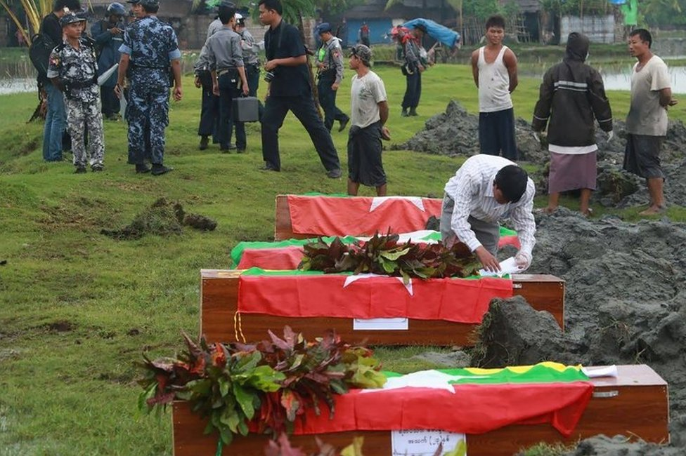 Myanmar border police prepare flag draped coffins bearing nine bodies of border guards killed in mysterious raids during a funeral ceremony at a cemetery in Maungdaw in Rakhine State on October 11, 2016.