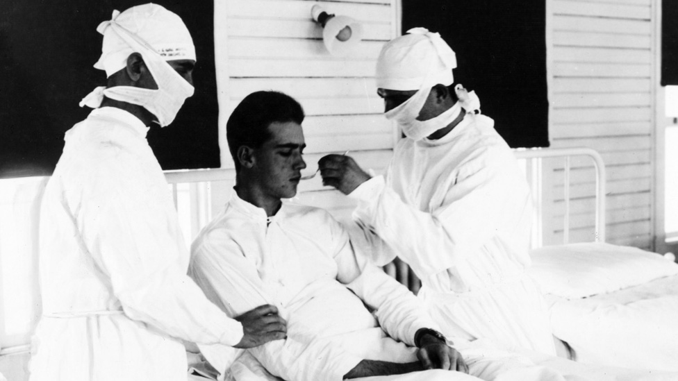 Doctors with a 1918 flu patient at a US naval hospital