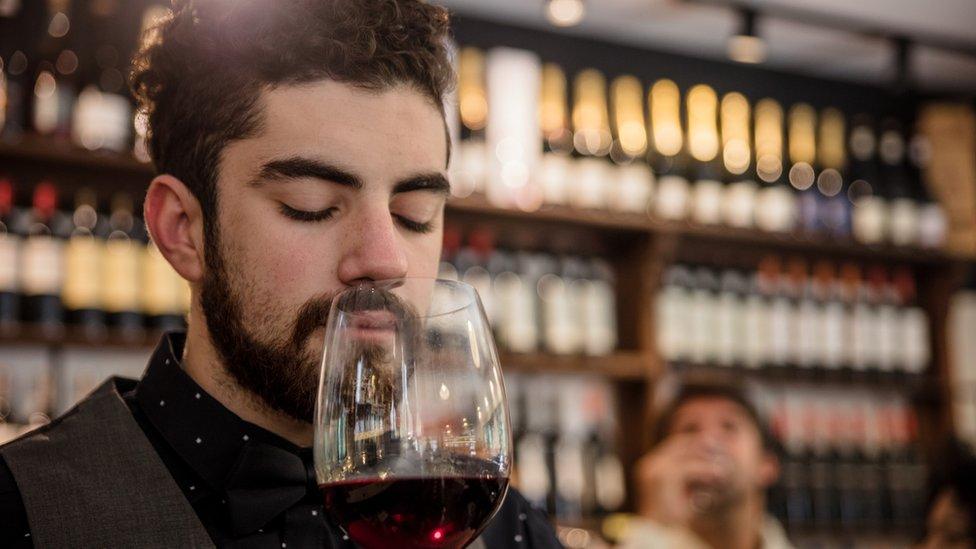 Men kiss a glass of wine.