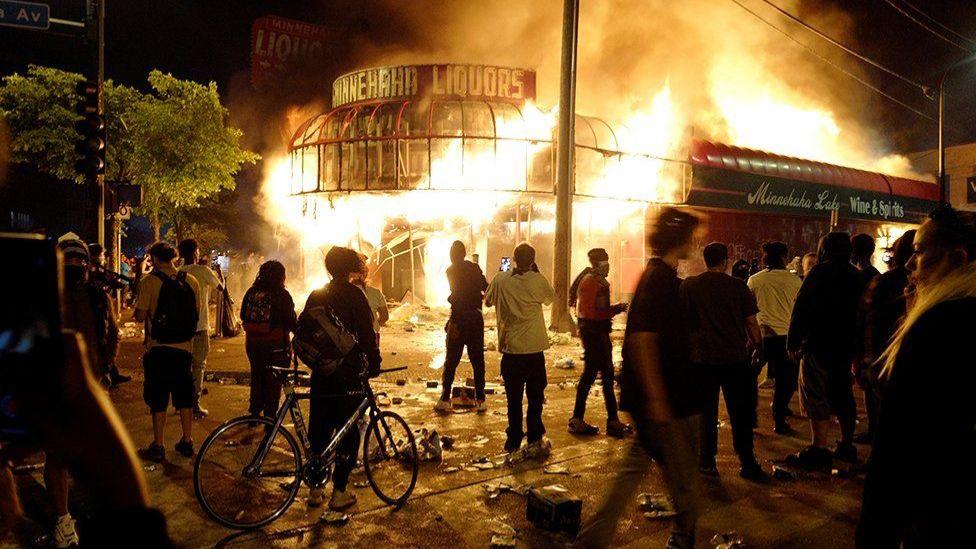 Personas observan el incendio de un negocio comercial.