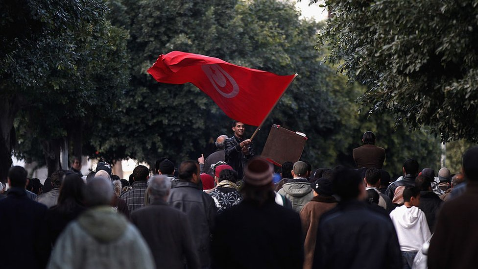 Tunisian man waves flad at demonstration