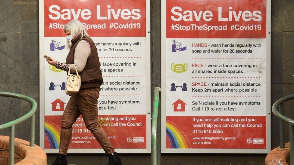 """Mujer en Londres pasando delante de un cartel en la calle que dice""""Cuídate y salva vidas"""""""