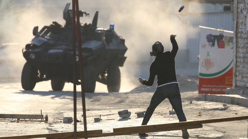 Protester hurls a glass bottle towards a security vehicle in Sitra, Bahrain on 14 February 2016