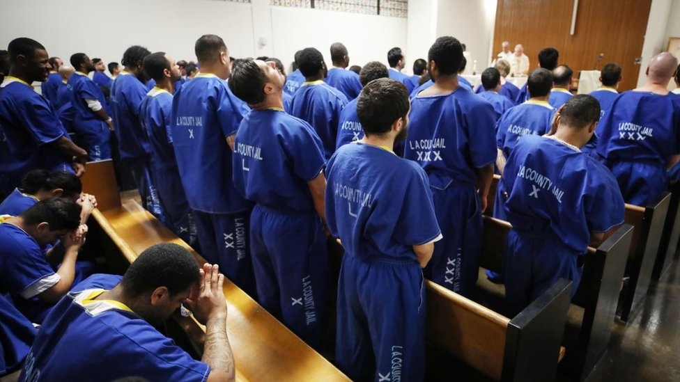 Inmates worship during Christmas Mass led by Archbishop Jose H. Gomez in a chapel at Men's Central Jail