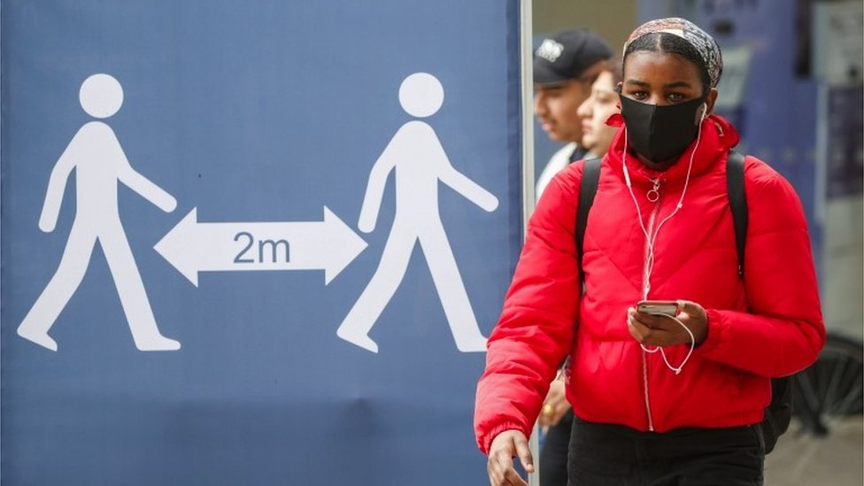 A woman walks past a sign calling for social distancing