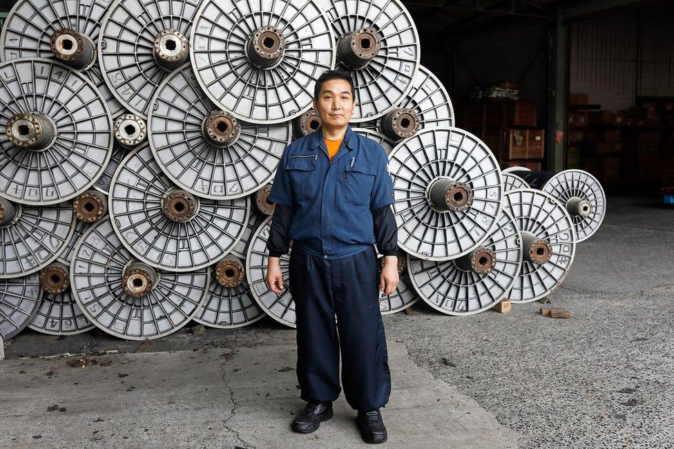A denim maker stands in a factory
