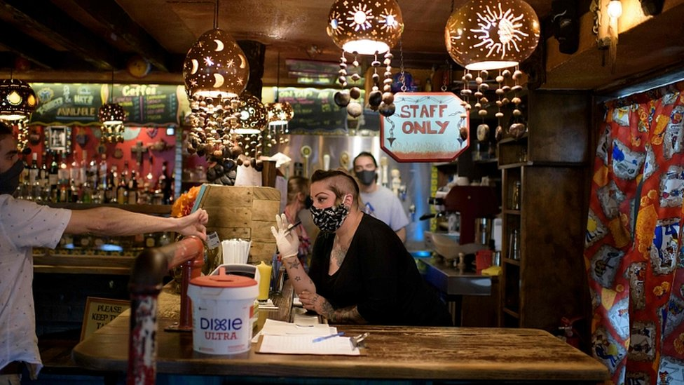 Bar staff check patrons` ID at Under the Volcano in Houston, Texas, on May 22, 2020