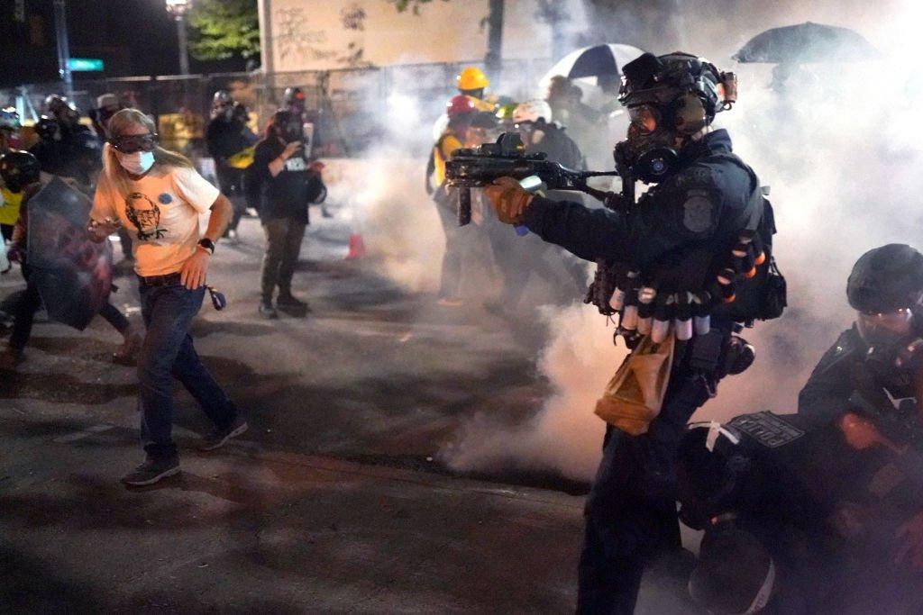 يوجه ضابط فيدرالي سلاحه إلى الحشد أثناء تفريق احتجاج ضد الظلم العنصري ووحشية الشرطة أمام محكمة مارك أو.هاتفيلد الأمريكية في الساعات الأولى من يوم 30 يوليو/تموز 2020 في بورتلاند، أوريغون، الولايات المتحدة.