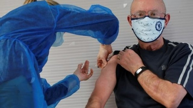 Un hombre recibe una vacuna contra la covid.